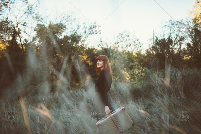 Young romantic model posing with suitcase in rural field looking romantically away