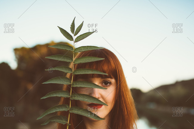 Portrait of ginger model with red lips posing playfully and covering eye with leaf