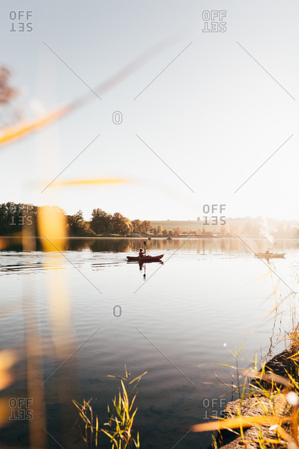Landscape of tranquil lake water in morning haze with traveler sailing in boat and rowing