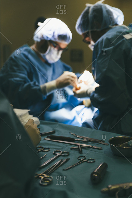 Assistant working with surgeons and providing them with instruments during operation