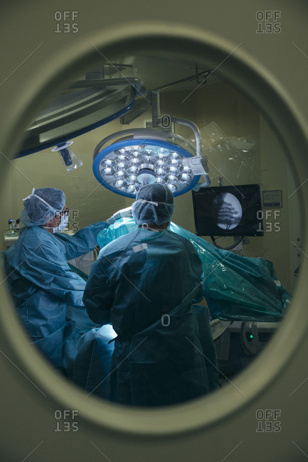 Shot through glass in door of professional medical staff working with patient in surgery