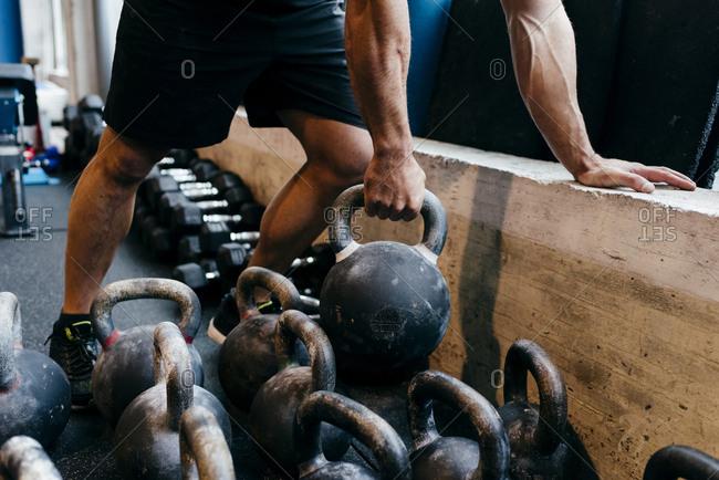 Crop man lifting weight