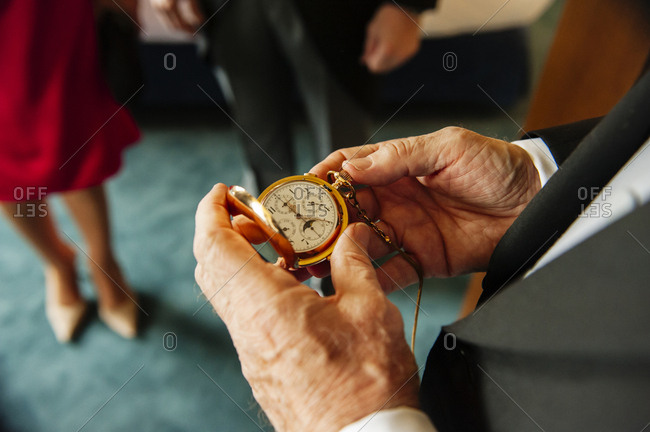 Faceless shot of old gentleman in suit watching pocket watch checking time