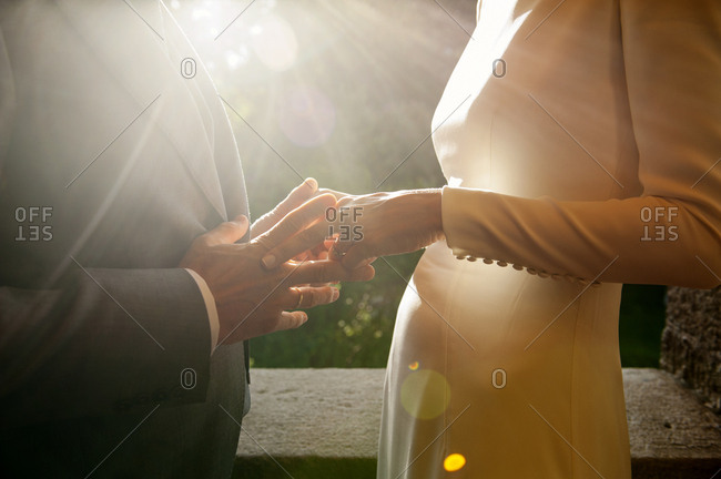 Faceless shot of elegant newlyweds touching hands gently in bright back light