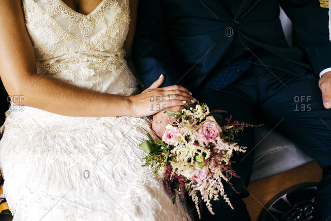Crop shot of woman and man in elegant wedding outfits sitting together on bench
