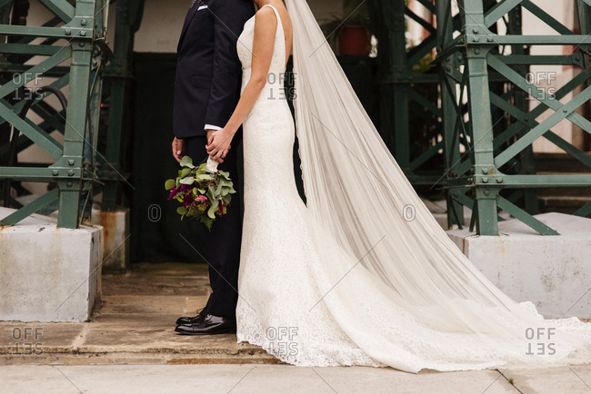 Crop stylish bride and groom posing