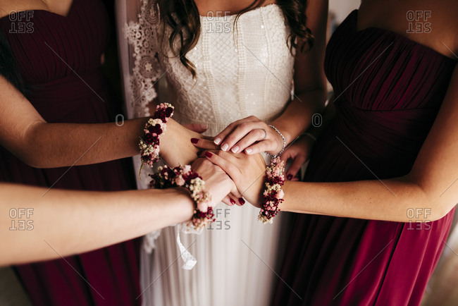 Unrecognizable bridesmaids standing around bride and holding hands together before wedding ceremony