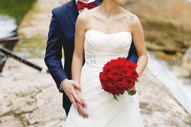 Unrecognizable bride and groom posing for camera in nature