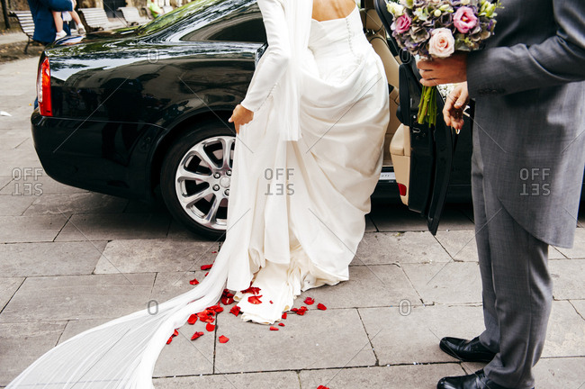 Unrecognizable bride getting into car after wedding ceremony and groom standing near her with bouquet