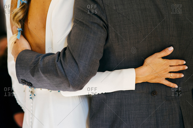 Unrecognizable bride and groom lovingly embracing each other