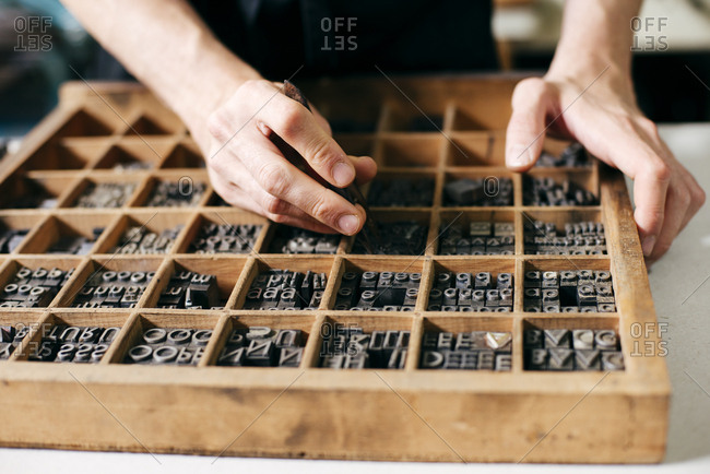 Crop worker arranging metal letter stamps in wooden box working in printing industry