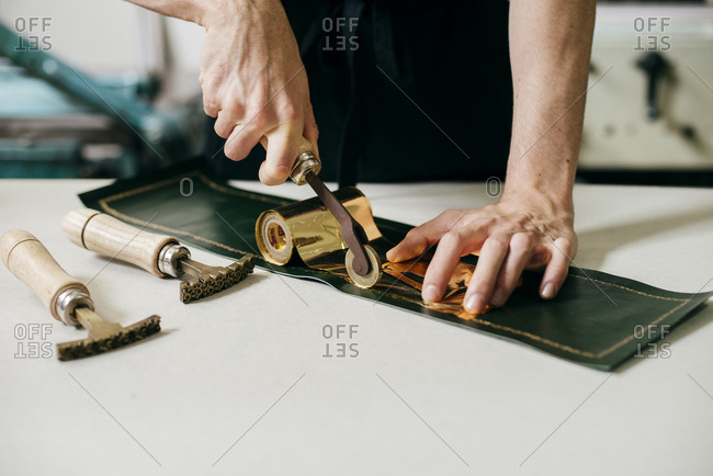 Crop shot of workman using tools and gold material while imprinting on leather