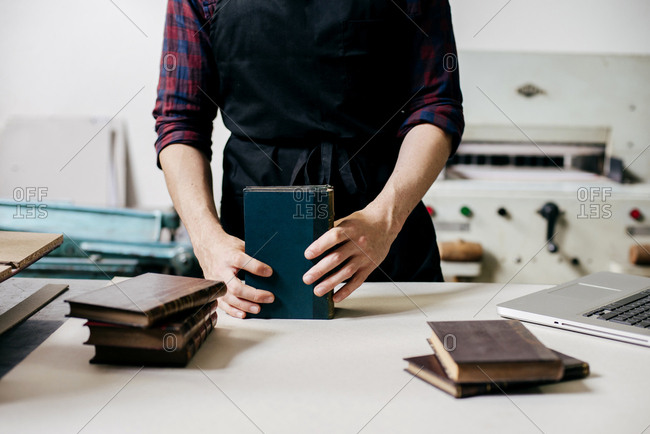 Faceless shot of man in apron arranging and creating leather notebooks