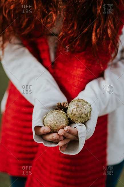 Crop woman in red scarf holding golden baubles and conifer cones in hands