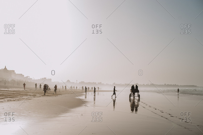 Landscape of tropical shoreline with sandy beach and people walking in haze of light