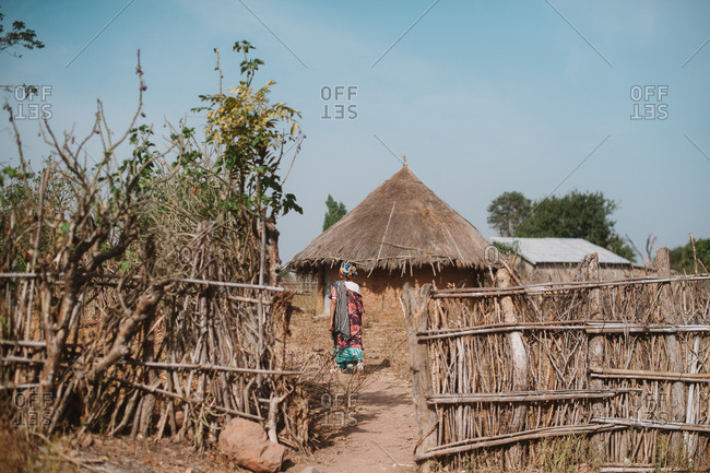 Exterior view of fence and thatched bungalows in native African village