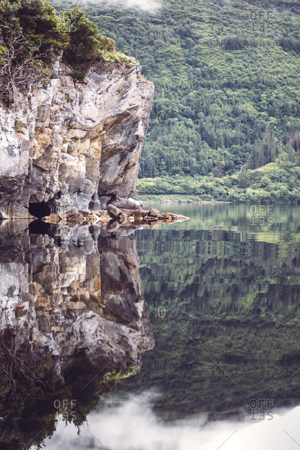 Rocky cliff on calm lake in Killarney National Park, Ireland