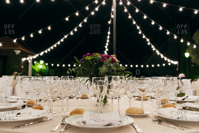 Beautifully decorated banquet table under small lights at night