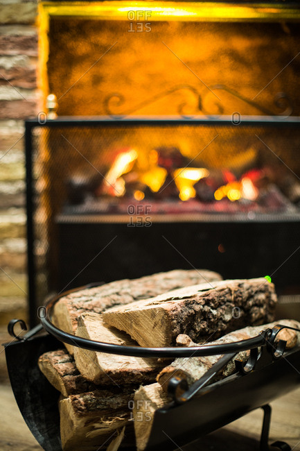 Stack of firewood composed near fireplace with burning flame at home