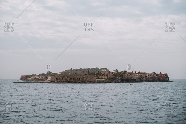 View of small town located on island in calm sea on cloudy day