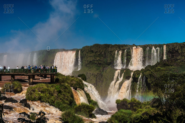 Iguazu, Brazil, South America - April 29, 2017: Visitors, drenched in spray, Garganta del Diablo (Devil's Throat), Iguazu Falls, UNESCO World Heritage Site