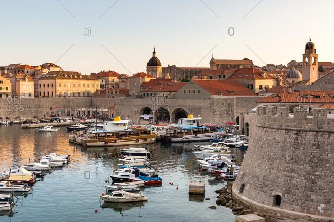 Dubrovnik, Croatia, Europe - June 5, 2017: Boats in Dubrovnik harbour during sunset, UNESCO World Heritage Site