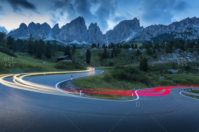Car trail lights on Passo Pordoi with mountain backdrop at dusk, Province of Bolzano, South Tyrol, Italian Dolomites, Italy, Europe