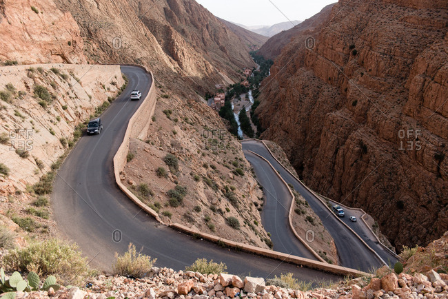 Dades Valley, Morocco - May 7, 2017: Vehicles traveling on winding road on mountainside in Dades Valley