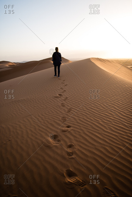 Woman walking in the desert sand, Merzouga, Morocco
