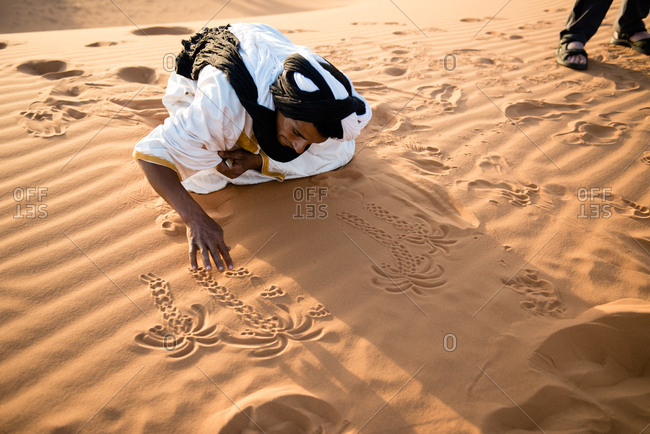 Merzouga, Morocco - May 8, 2017: Man drawing in desert sand