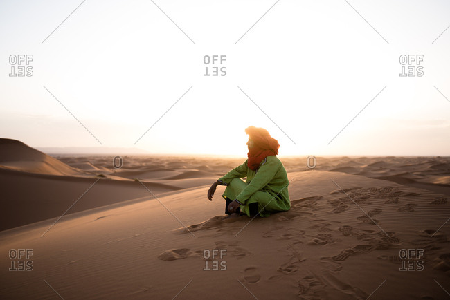 Merzouga, Morocco - May 8, 2017: Man sitting in the Erg Chebbi at sunset