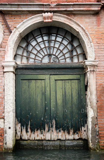 Exterior of building with green door along the canal in Venice, Italy