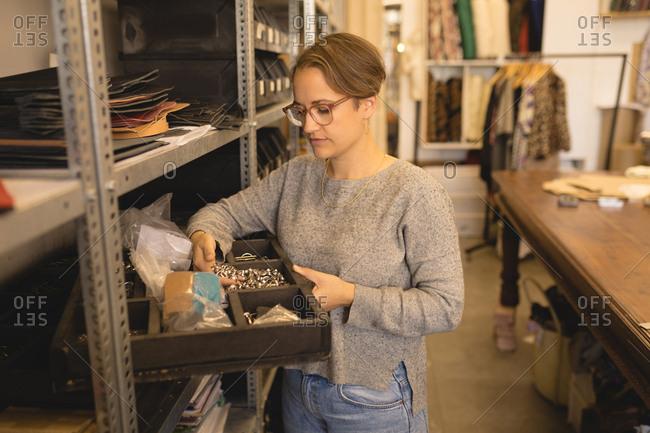 Female worker looking at tools in workshop