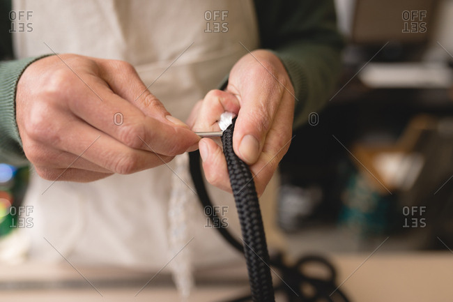 Mid section of worker making leather straps in workshop
