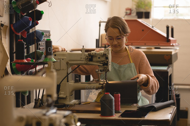 Female worker sewing leather in workshop
