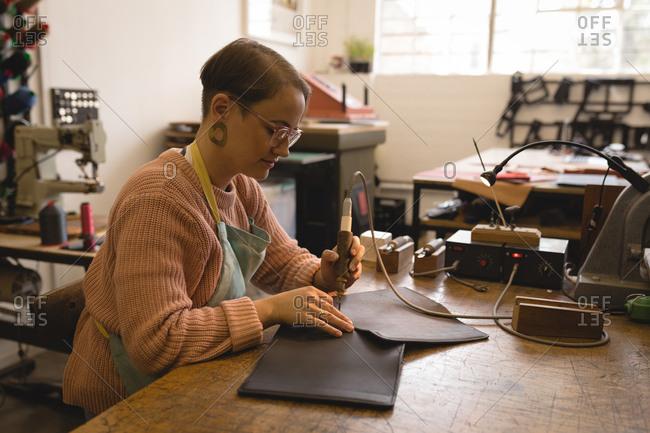 Worker stitching leather with stitching machine in workshop