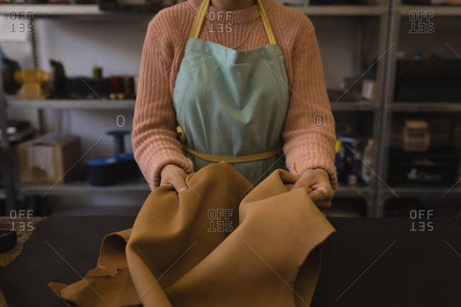 Mid section of worker holding leather in workshop