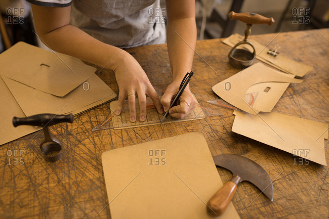 Mid section of worker marking on leather in workshop