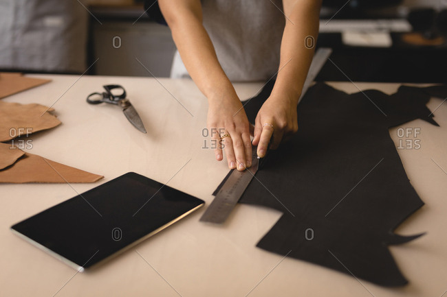 Mid section of worker measuring leather with ruler in workshop