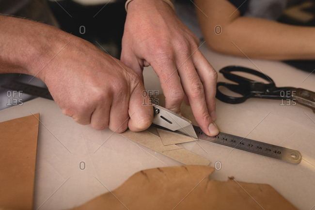 Worker cutting a leather with cutter in workshop