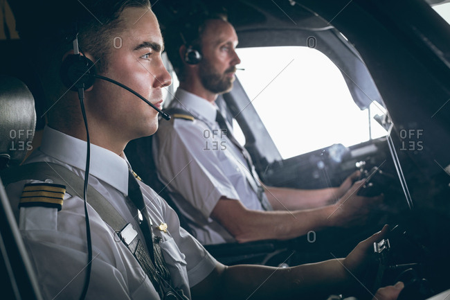 Side view of pilot and copilot flying an airplane