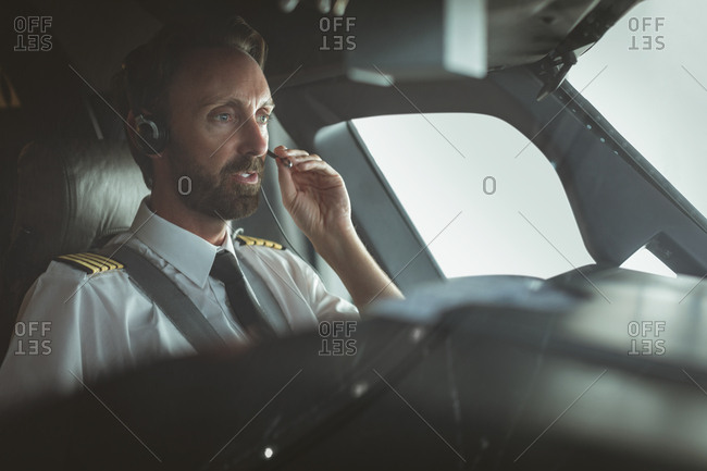 Attentive pilot talking on headset while flying an airplane
