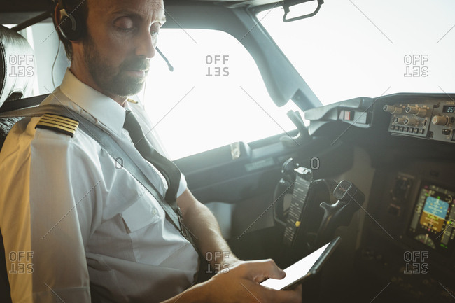 Concentrated pilot using digital tablet in airplane