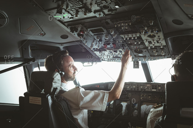Attentive pilot adjusting controls while copilot flying an airplane