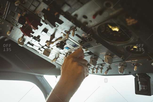 Hand of pilot adjusting controls while flying an airplane