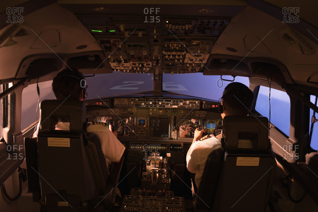Rear view of pilot and copilot flying an airplane
