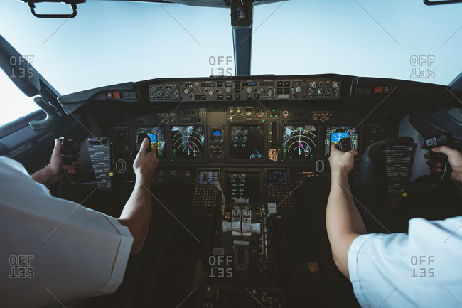 Mid section of pilot and copilot flying an airplane