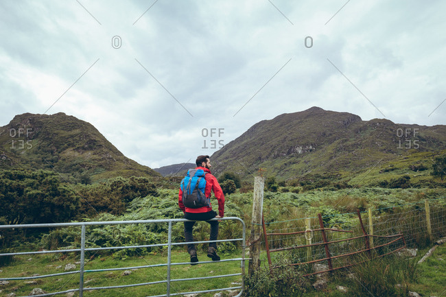 Rear view of male hiker sitting on the fence on countryside landscape