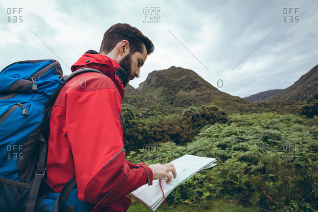 Close-up of male hiker reading the map near the green hills