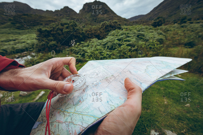 Close-up of hiker reading the map near the green hills